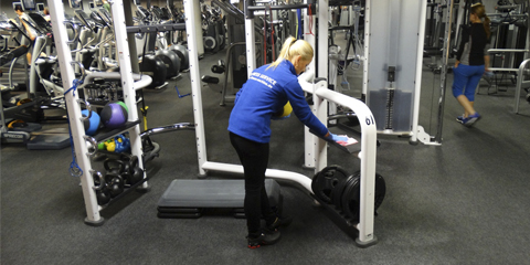 Woman cleaning stationary bike in fitness center
